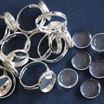 10 Silver Plate Rings And Glass Domes.